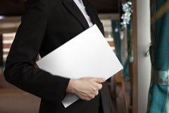 La señora del negocio sostiene la revista blanca foto de archivo libre de regalías