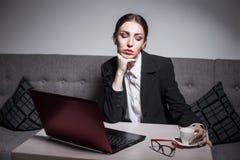 La señora del negocio vestida en traje y con el ordenador portátil tiene un descanso para tomar café Fotografía de archivo libre de regalías