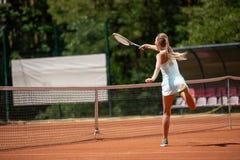La señora delgada está jugando a tenis en corte imagenes de archivo