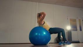 La señora deportiva está haciendo ejercicios del Situps en un Fitball mientras que entrena en el gimnasio almacen de video