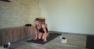 La señora deportiva se prepara para comenzar una lección de la yoga que ella se relajó en la estera del deporte en el piso la con almacen de video
