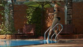 La señora en bikini se coloca sube reunir las escaleras del metal