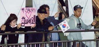 La señora en la reunión lleva a cabo una muestra que diga, ` que amamos el arma-Hye del parque ` Imagen de archivo