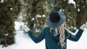 La señora en sombrero y capa verdes gira debajo de la nieve que cae en el bosque almacen de metraje de vídeo