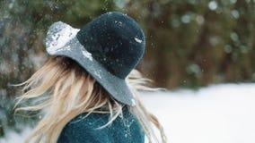 La señora en sombrero y capa verdes se coloca debajo de la nieve que cae en el bosque almacen de metraje de vídeo
