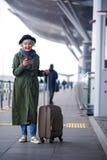 La señora envejecida positivo está sosteniendo el teléfono móvil con sonrisa fotos de archivo libres de regalías