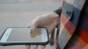 La señora está caminando en el camino y está utilizando la navegación App en su Smartphone almacen de video