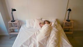 La señora está despertando en un dormitorio acogedor y está apagando el despertador en su teléfono almacen de metraje de vídeo