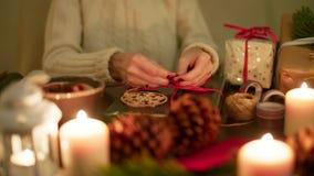 La señora está envolviendo un regalo de Navidad con la cinta roja 4K festivo agradable que se calienta metrajes