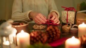 La señora está envolviendo un regalo de Navidad con la cinta roja 4K festivo agradable que se calienta Fotografía de archivo