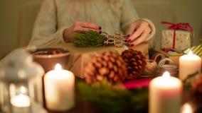 La señora está envolviendo un regalo de Navidad en la tabla festiva adornada 4K almacen de metraje de vídeo