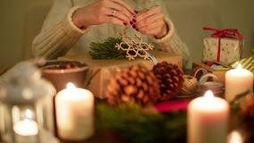 La señora está envolviendo un regalo de Navidad en la tabla festiva adornada 4K Imágenes de archivo libres de regalías