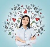La señora está pensando en compras Los iconos coloridos de las compras están volando en el aire Imágenes de archivo libres de regalías