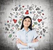 La señora está pensando en compras Los iconos coloridos de las compras se dibujan en el muro de cemento Fotografía de archivo libre de regalías