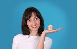 La señora está sosteniendo la casa de madera imagen de archivo