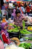 La señora examina verduras como bazar del mercado de la comida fresca en Hatyai Tailandia Fotografía de archivo