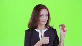 La señora hace publicidad del bitcoin y muestra los pulgares para arriba Pantalla verde almacen de metraje de vídeo