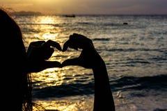 La señora hace una muestra del corazón de su mano con el mar y el backg de la luz del sol Fotografía de archivo