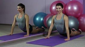 La señora hermosa con el cuerpo atractivo del ajuste que estira en el gimnasio, haciendo flexibilidad ejercita almacen de metraje de vídeo
