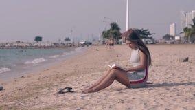 La señora hermosa con el pelo oscuro largo lee el libro en la playa de la arena metrajes