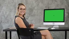 La señora hermosa del negocio en oficina está mirando la cámara y la sonrisa Exhibición verde de la maqueta de la pantalla metrajes
