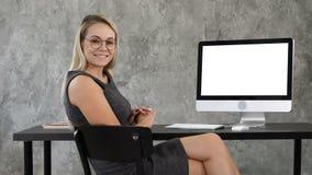 La señora hermosa del negocio en oficina está mirando la cámara y la sonrisa Visualización blanca metrajes