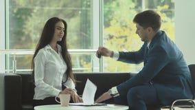 La señora hermosa hace un trato acertado con el encargado en la oficina almacen de metraje de vídeo