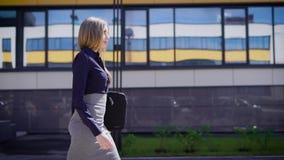 La señora hermosa joven en blusa azul y falda gris con el tablero en manos está caminando al aire libre cerca del edificio de ofi almacen de metraje de vídeo