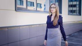 La señora hermosa joven en blusa azul y falda gris está caminando al aire libre a lo largo del edificio de oficinas moderno que l almacen de metraje de vídeo