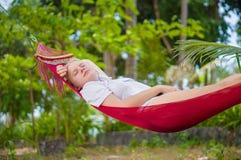 La señora joven agradable escucha música en morón debajo de árboles del plam en trop Imagen de archivo libre de regalías