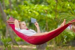 La señora joven agradable escucha música y leyó el libro en lector de la e-tinta en h Foto de archivo libre de regalías