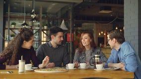 La señora joven atractiva alegre está contando historia divertida a sus amigos en el almuerzo en café, la gente está riendo y metrajes