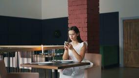 La señora joven bonita está esperando a su novio en el restaurante que se sienta en la tabla, usando smartphone entonces comproba almacen de video