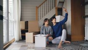 La señora joven bonita y su marido están haciendo llamada video en línea con smartphone durante la relocalización La gente es el  metrajes