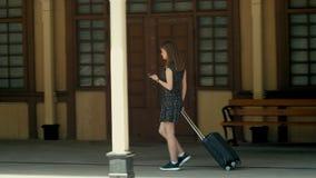 La señora joven con la maleta está caminando en la estación cinemática con el teléfono usando el App almacen de metraje de vídeo