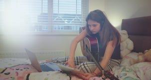 La señora joven concentrada con una guitarra en su dormitorio, la hace una búsqueda en su movimiento de la tableta entonces a su  metrajes