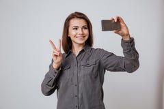 La señora joven de Cheeful hace el selfie por el teléfono móvil Imágenes de archivo libres de regalías