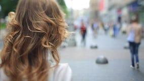 La señora joven de la moda atractiva en vaqueros y zapatos rojos elegantes camina en la calle urbana a través de la muchedumbre almacen de metraje de vídeo
