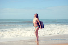 La señora joven de la persona que practica surf hermosa en la playa con bodyboarding, alista para la diversión Imágenes de archivo libres de regalías