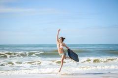 La señora joven de la persona que practica surf hermosa en la playa con bodyboarding, alista para la diversión Fotos de archivo libres de regalías