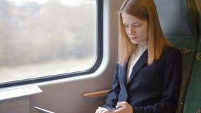 La señora joven del negocio está trabajando en su ordenador portátil y está utilizando su teléfono en tren almacen de video