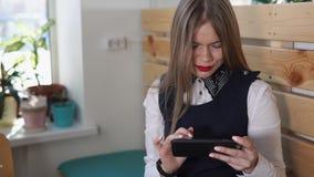 La señora joven del negocio lee las últimas noticias de la moda en su teléfono móvil almacen de metraje de vídeo