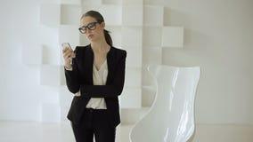 La señora joven del negocio se coloca con un móvil cerca de una silla blanca en una oficina blanca futurista almacen de video