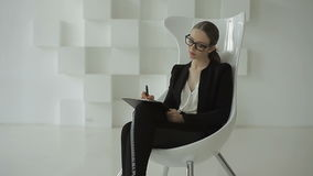 La señora joven del negocio sienta y escribe algo en su cuaderno en una oficina blanca futurista metrajes