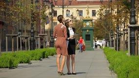 La señora joven del negocio vende un objeto de las propiedades inmobiliarias a su cliente en un parque metrajes