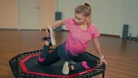 La señora joven deportiva está haciendo estirando ejercicios en el entrenamiento de la aptitud en el gimnasio metrajes