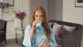 La señora joven en vestido azul viene más cerca y bebe la leche almacen de video