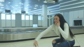 La señora joven encuentra a su amigo en la correa del equipaje almacen de metraje de vídeo
