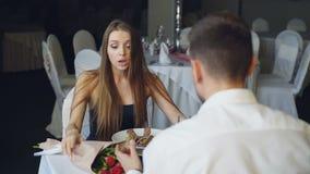 La señora joven enojada está discutiendo con su novio mientras que cena en el restaurante entonces que se va Pelea de los amantes metrajes