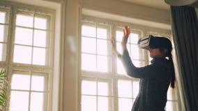 La señora joven está disfrutando de nueva experiencia en la situación móvil de los brazos y del cuerpo de los vidrios de la reali metrajes